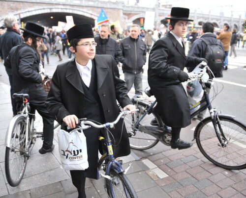 Three Orthodox Jews on their bicycle look at Democratic Republic of Congo demonstrators staging a protest on December 23, 2011, in downtown Antwerp. Congolese immigrants hold a demonstration to denounce the re-election of President Joseph Kabila in their native Democratic Republic of Congo, days after a similar protest in Brussels. AFP PHOTO  / GEORGES GOBET (Photo credit should read GEORGES GOBET/AFP/Getty Images)